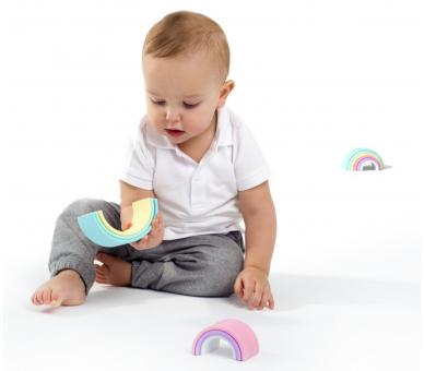 Bebé jugando con arco iris en tonos pastel de Dëna