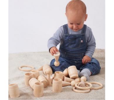 Bebé jugando con materiales de madera juego heurístico