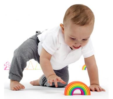 Bebé jugando con el arco iris en tonos vivos de silicona de Dëna
